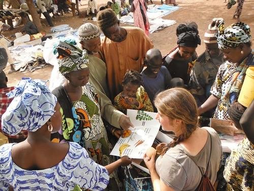 A Peace Corp Volunteer shows community members a brochure.