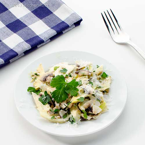 Shaved Artichoke and Mushroom Salad on plate with napkin and fork