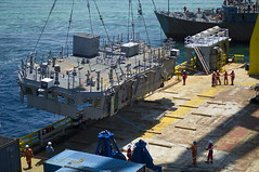 The U.S. Navy contracted vessel M/V Jascon 25 and its salvage crew guides the second deck level of USS Guardian (MCM 5) onto the deck of the vessel, March 2 in the Sulu Sea. (U.S. Navy photo by Mass Communication Specialist 1st Class Anderson Bomjardim)