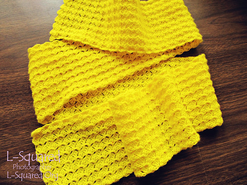 Bright yellow scarf made up of a stitch texture that looks and feels like tiny flower petals.