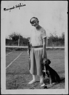 Margaret Hopkins with a tennis racquet and a dog at her side / Margaret Hopkins tenant une raquette, un chien à ses côtés