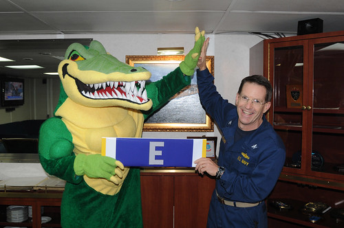 "USS Peleliu's mascot presents Capt. John D. Deehr, commanding officer, a large Battle ""E"" ribbon"