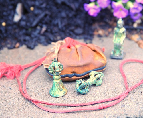 Contents of an old Tibetan Buddhist blessing bag, dorje, bell, statue of Maitreya, the Buddha of the future seated, blessing cord, bag, Garden for the Buddha, Seattle, Washington, USA by Wonderlane