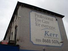 "A sign painted on the side of an end-of-terrace building, with a white background and a light blue border.  The text is mostly in grey, but the same light blue is used for the name ""Kerr"" and for a curved line under the word ""everyone"".  The text reads: ""Professional Eye Care for everyone.  Kerr Optometrists.  (020) 8688 5076""."
