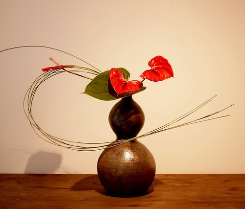 Simple Ikebana Art in a Container on a Wooden Table