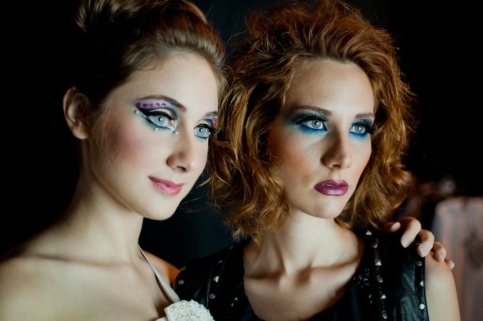 Dos modelos completamente maquilladas posan para las cámaras minutos antes de salir a sus respectivos desfiles. (Elton Núñez)