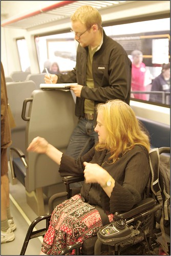 Photo of wheelchair user providing reaction to interior of new commuter rail car mock up