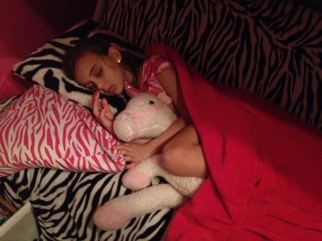 Karli cuddling her unicorn