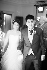 groom(0.0), bride(1.0), bridal clothing(1.0), groom(1.0), wedding reception(1.0), wedding(1.0), photograph(1.0), male(1.0), marriage(1.0), man(1.0), monochrome photography(1.0), woman(1.0), formal wear(1.0), wedding dress(1.0), monochrome(1.0), black-and-white(1.0), person(1.0), ceremony(1.0),