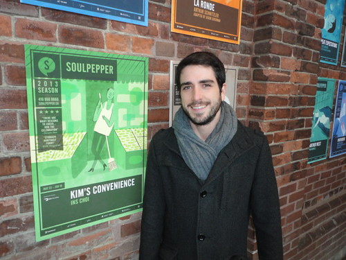 Joel Levy beside green poster of theatre show in Toronto