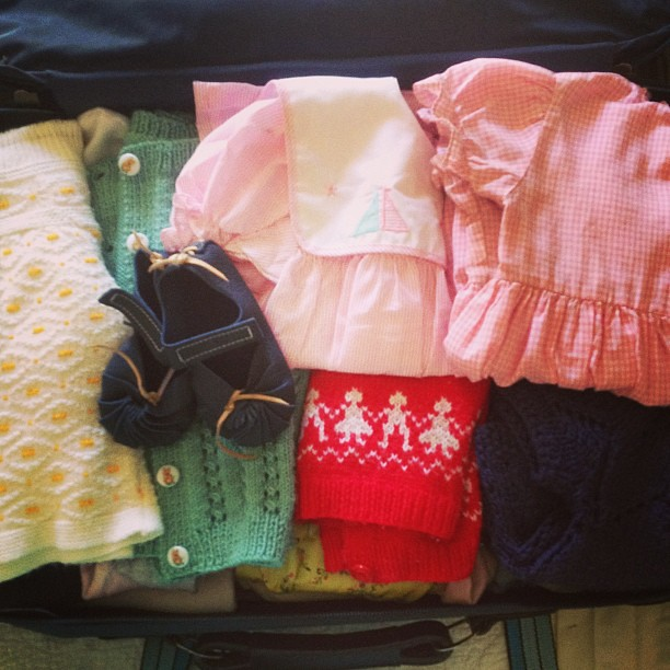 Packing the girl: hand knits, overalls, vintage dresses, tights and onesies.