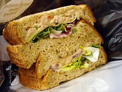 A sandwich on thick slices of brown bread, with a layer of tuna mayonnaise and crisp lettuce in between. The sandwich has been cut in half and the two halves placed on top of each other.
