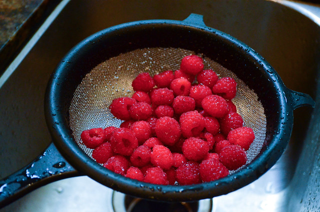 Raspberries being washed in a colander.
