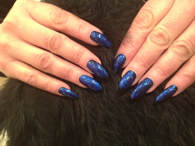 Acrylic nails with navy blue polish with blue glitter ...