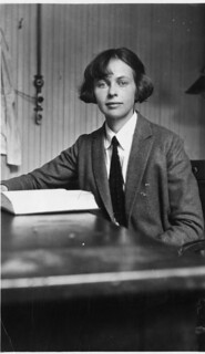 young woman seated at desk in coat and tie