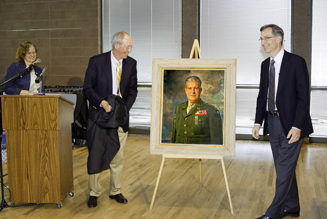 Heather McClenahan and Mike Wheeler of the Los Alamos Historical Society unveil the portrait with Charlie McMillan, director of Los Alamos National Laboratory