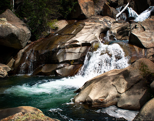 Colorado Rocky Mountain waterfall cascades over boulders and rocks into an aqua blue pool