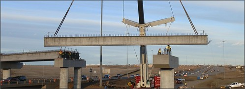 Photo of crane lifting girder into place on Peña Boulevard rail bridge