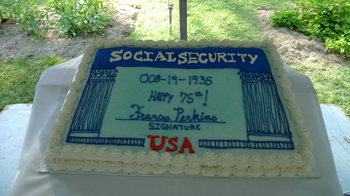 A rectangular cake sits on top of a table. The cake is decorated like a social security card. It says Social Security at the top, with the numbers 008-14-1935, Happy 75th!, with Frances Perkins written above a signature line.