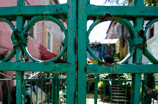 A colorful and spider-webbed gate on the island of Burano, Italy.