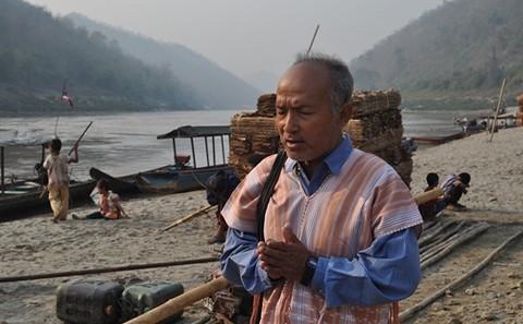 在3月中旬的國際河流活動日中,一名牧師在薩爾溫江(即怒江東南亞段)邊祈禱。 圖片來源:kesan.asia