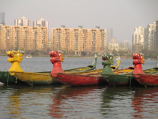 Four colourful dragon boats on a lake in Nanjing.