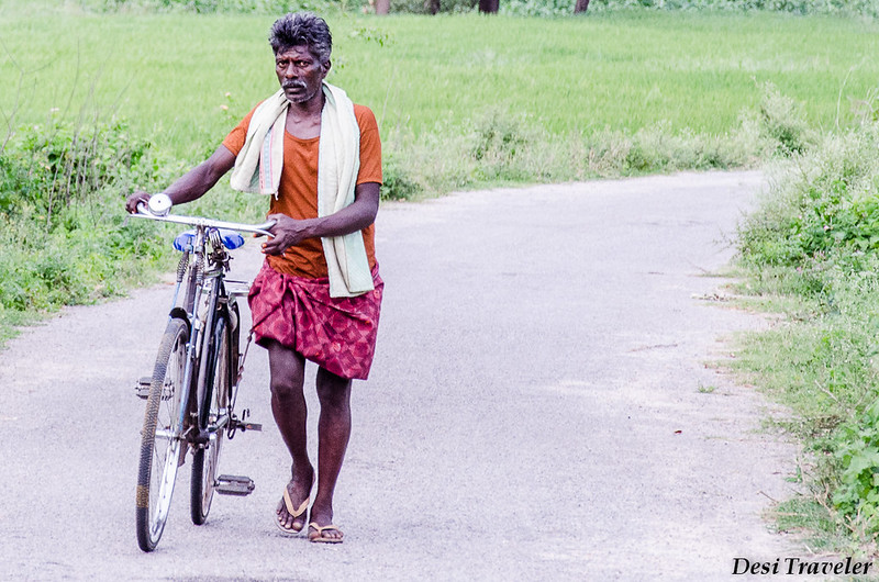 A Cyclist Walking with his Cycle