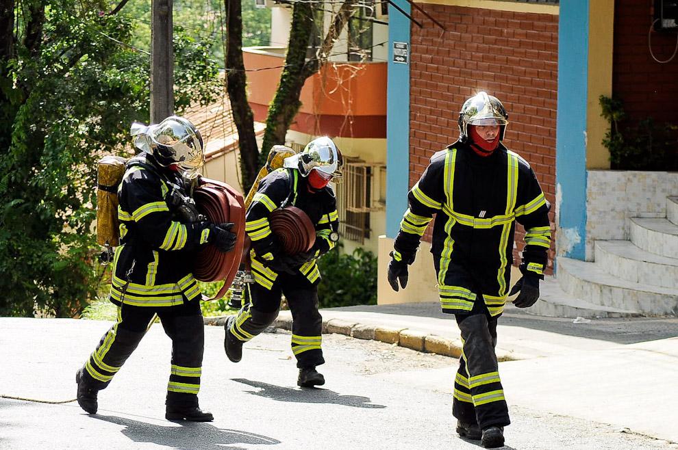 """Tres bomberos franceses, miembros de """"Action Pompiers Pour l'Urgence Internationale"""" (APPUI), quienes llegaron de Lyon para un primer curso de formación de incendio de 10 días para los Bomberos Voluntarios del Paraguay, hacen demostración de sus habilidades y sus técnicas. La Tercera Compañía """"Sajonia"""" fue sede y anfitrión de dicho curso, donde los bomberos franceses, ejerciendo sus permisos correspondientes, se fusionaron con los bomberos locales y trabajaron en servicios reales. (Elton Núñez)"""