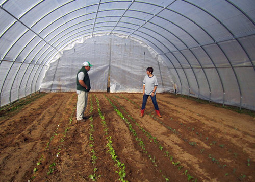 Johnson County, Tenn. District Conservationist, Jason Hughes, talks with landowner Janet Mahala about her recently constructed high tunnel. NRCS photo by Michelle Banks.