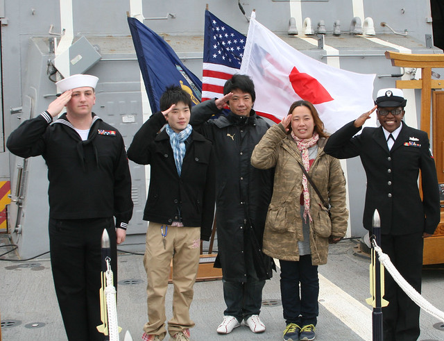 YOKOSUKA, Japan - U.S. Navy Electronics Technician 3rd Class Joseph Hochman, left, and Interior Communications Electrician 3rd Class Zaquavius Grissom pose for a photo with Japanese visitors aboard USS Mustin.