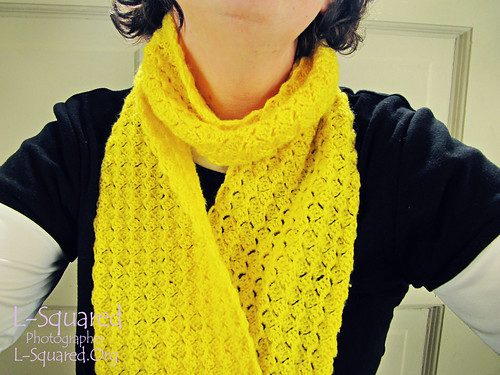 Yellow petals scarf being modeled around a person's neck.