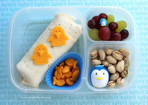 EasyLunchboxes penguin lunch - deli burrito, grapes, pistachios, goldfish crackers.