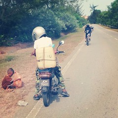 Along the expressway to Desaru,  a few of us were mystified by this scene we rolled by. What we thought was a trained monkey was actually a child in brown clothing being directed by his father to pick up something from the roadside. What that be?