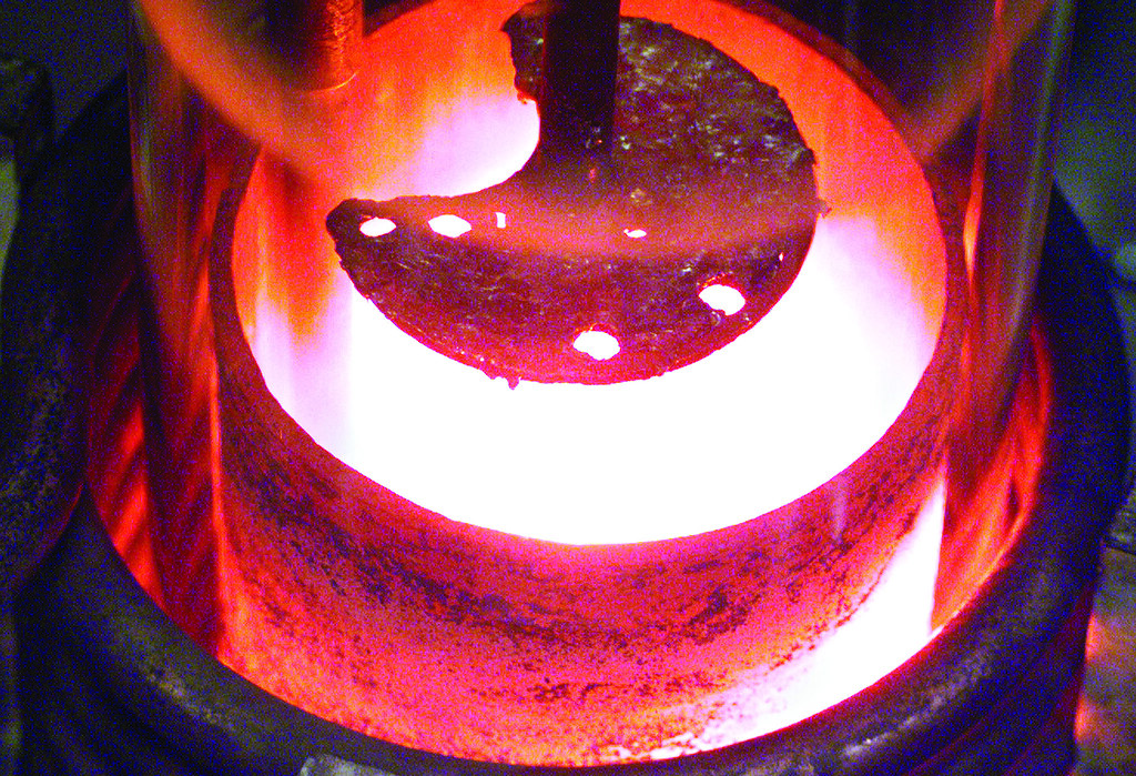 Molten plutonium in a crucible. The improved processing of old plutonium generates less than half of the waste of the former process.