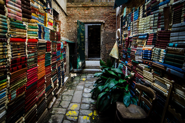 An open air hallway lined with books between rooms at Libreria Acqua Alta.