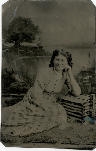 Smiling Woman Leaning on a Model Log Cabin - Tintype