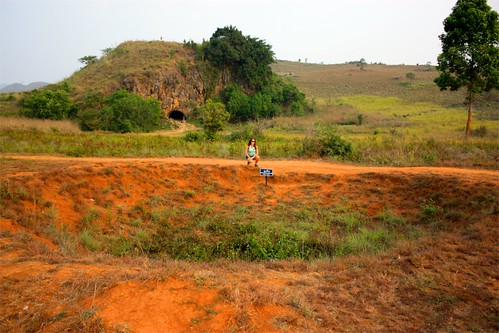 a bomb crater made sometime between 1964 and 1973. in the background, a cave that used to be creamatorium in the day of the jars