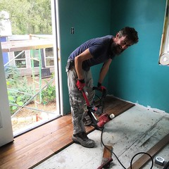 Aidan Furey puts down reclaimed long leaf pine boards on the floor of our guest room.