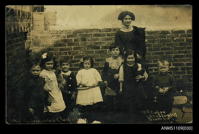 Photographic postcard of a female teacher with her kindergarten class at Miss Capon's Private School in Southsea, Portsmouth
