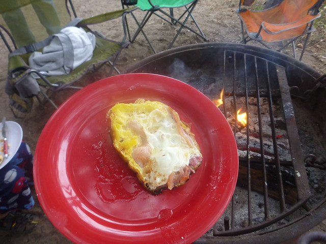 Just-cooked fried edds and bacon on a red plate over a grated campfire.