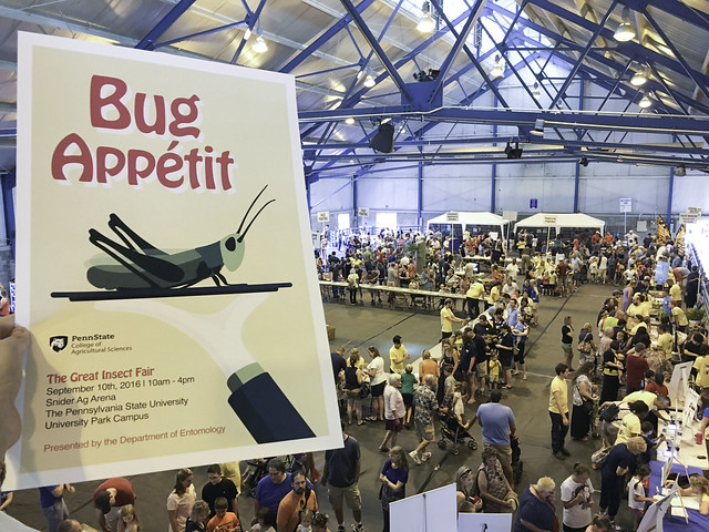 Photo advertising the Great Insect Fair at Penn State Univeristy, September 10th 2016. Held up and beyond is the fair in action. Lots of people moving about from table to table in a large building.