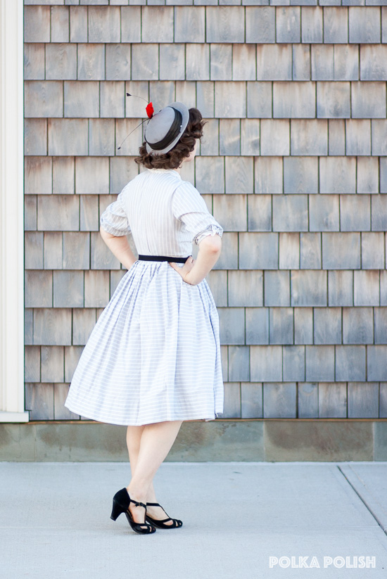 Back of a gold and grey 1950s day dress paired with black shoes and a grey hat with orange and black feathers