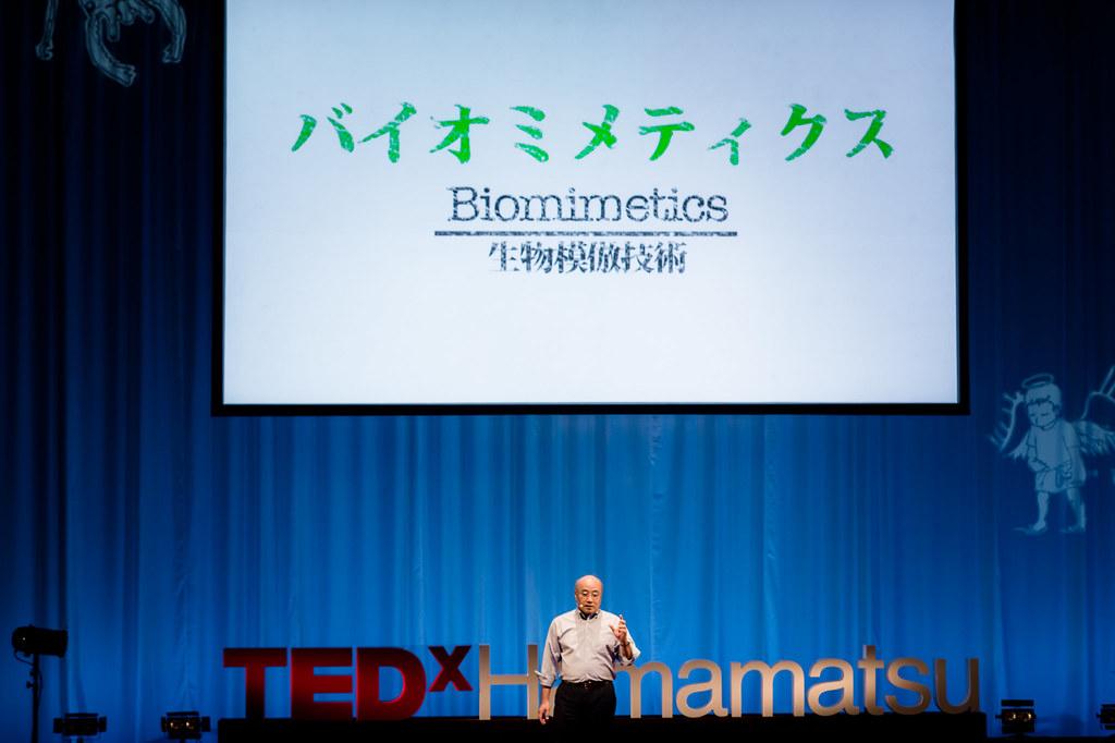 写真:バイオミメティクスという文字が映し出されたスクリーンを背に、スピーチをする針山さん
