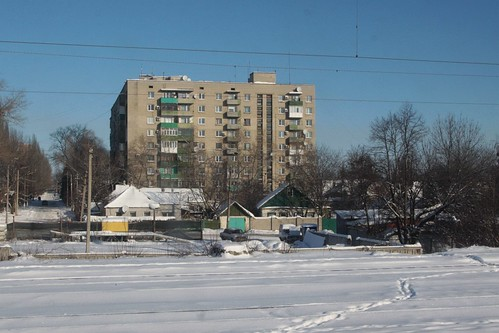Soviet-era apartment blocks tower over older cottages