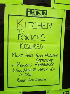 "A neon-yellow poster with a printed ""Plan Personnel"" header and writing in black pen: ""Kitchen Porters Required. Must have food hygiene certificate + previous experience. Will need to apply for a CRB. Please see Georgie."""