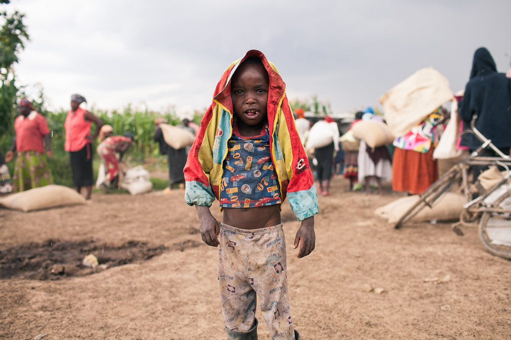 a child stands in the rain as members of the pipeline idp camp collect their corn rations