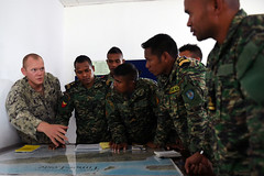 U.S. Navy Engineering Aide 3rd Class Quinton Schnarrs, assists members of the Forsa Defesa Timor-Leste (F-FDTL) in putting together a course of action for a simulated mission plan during CARAT Timor-Leste.  (U.S. Navy/MC1 Rosalie Chang)