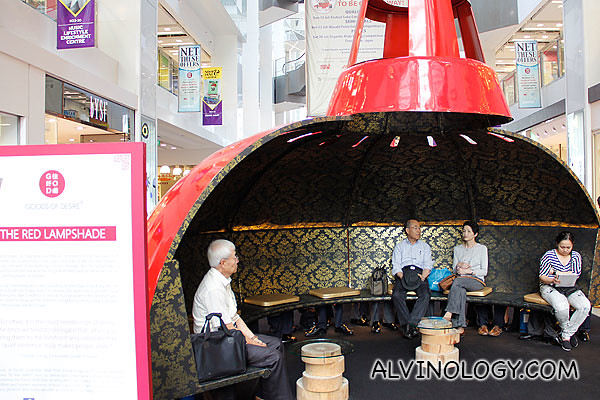 Red lampshades for shoppers to rest their feet (old folks not part of exhibit)