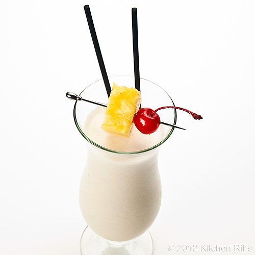 Piña Colada Cocktail with Pineapple and Maraschino Cherry Garnish, White Background