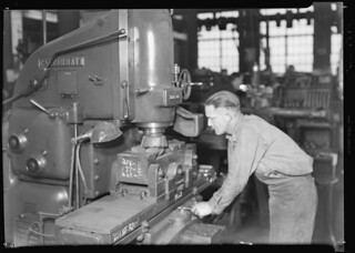 This skilled machinist is running a machine which faces off the mould and carves it to the shape of the bottle, March 1937